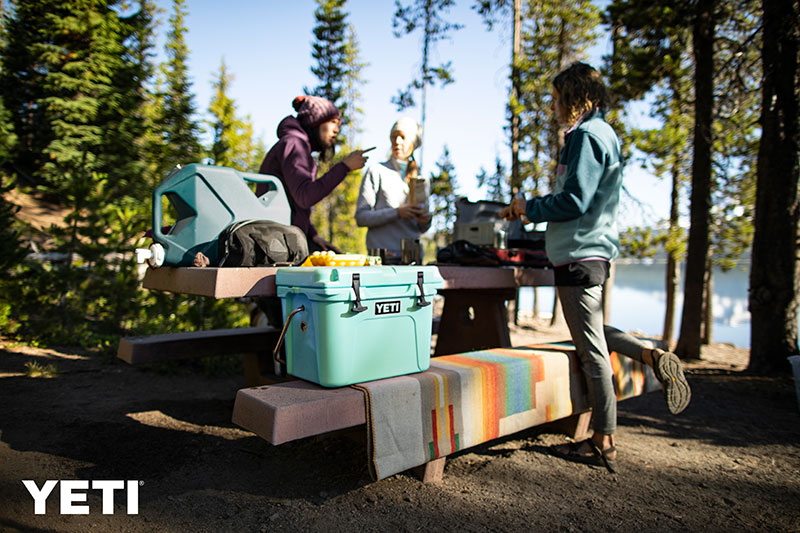 An image of campers in the outdoors with a Yeti cooler