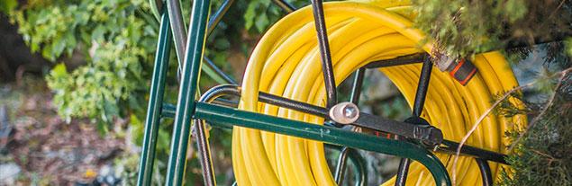 A closeup of a yellow hose outside.