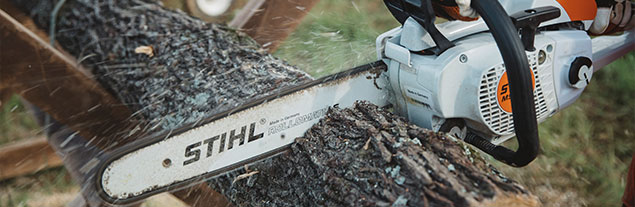 A Stihl chainsaw cutting through wood.