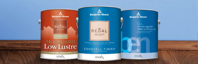 Benjamin Moore paint cans in front of a freshly painted blue wall.