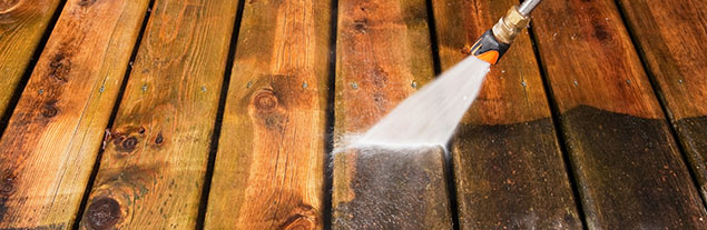 Pressure washing a wooden floor.